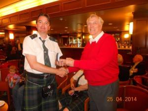 Retired President George Brown accepts his Life Membership from a disheveled Pipe Major Angus Beath